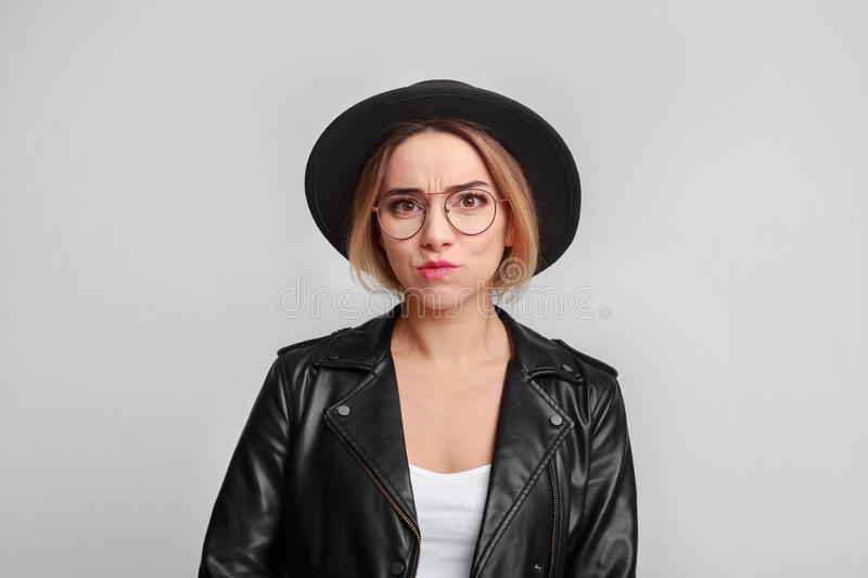 Nadenkende vrouw die leerjasje en oogglazen dragen stock foto's