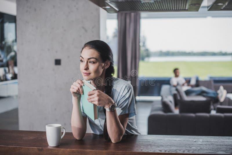 nadenkende vrouw die met boek weg tafelblad met koffiekop bekijken terwijl haar vriend stock afbeeldingen