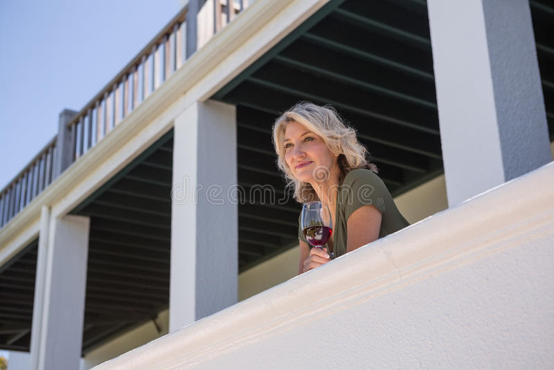 Nadenkende vrouw die wit wijnglas in balkon houden bij restaurant royalty-vrije stock fotografie