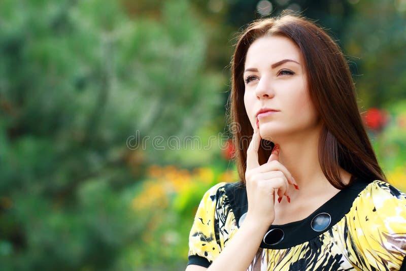 Nadenkende vrouw in openlucht stock afbeelding