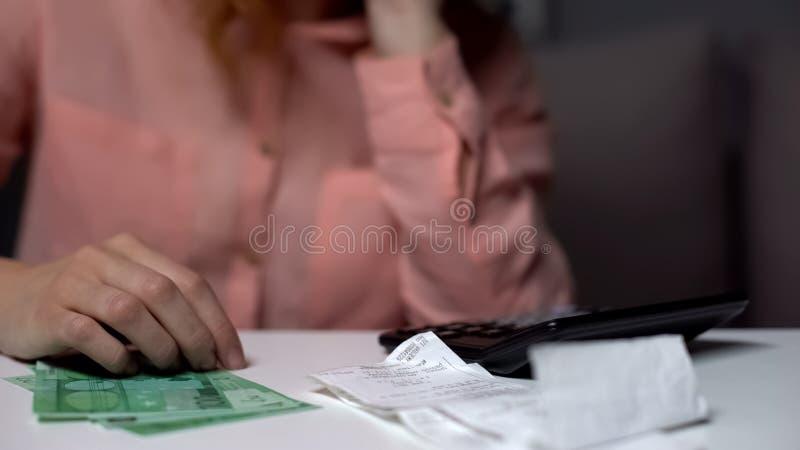 Nadenkende vrouw planningsbegroting, ontvangstbewijzen en calculator op lijst, euro rekeningen royalty-vrije stock afbeelding