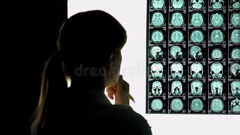 Nadenkende vrouwelijke arts die hersenenaftasten, medisch onderzoek, moeilijk geval analyseren stock afbeeldingen