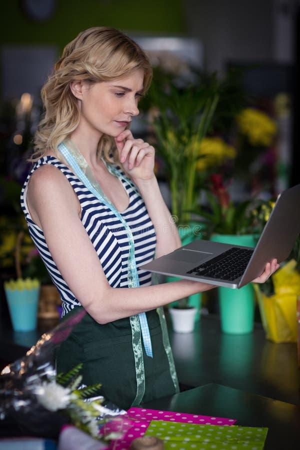 Nadenkende vrouwelijke bloemist die laptop bekijken stock afbeeldingen