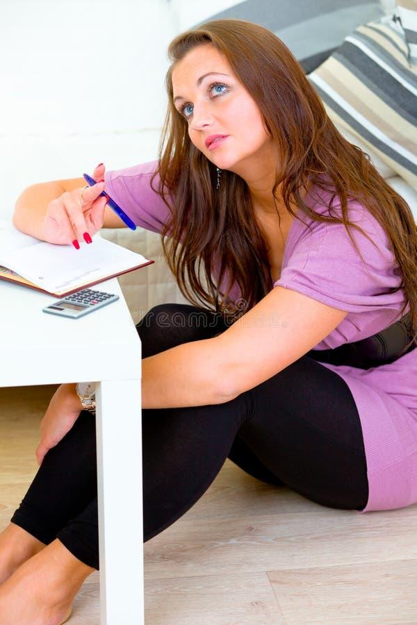 Nadenkende vrouwenzitting op vloer en het maken van nota's stock foto's