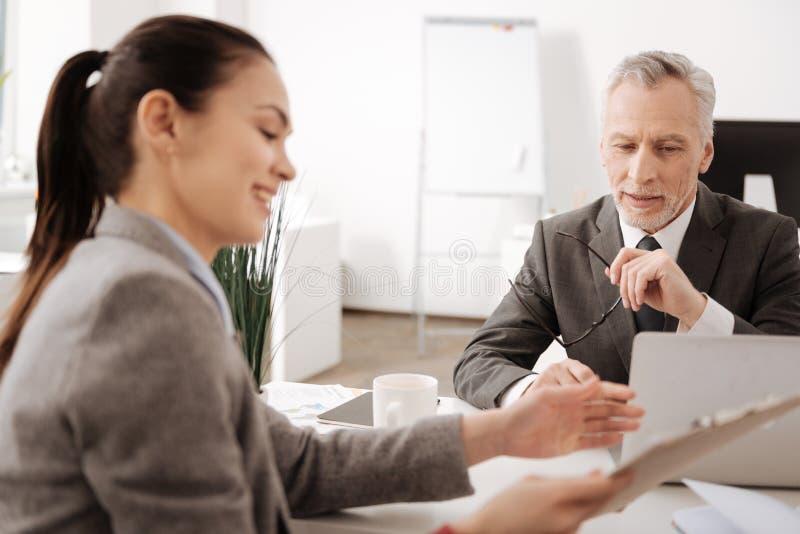 Nadenkende werkgever die aan zijn secretaresse luisteren stock fotografie