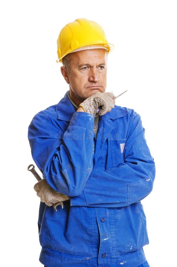 Nadenkende werkman met hulpmiddelen stock afbeelding