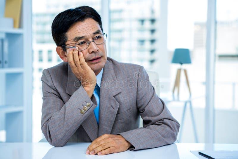 Nadenkende zakenman bij zijn bureau stock fotografie