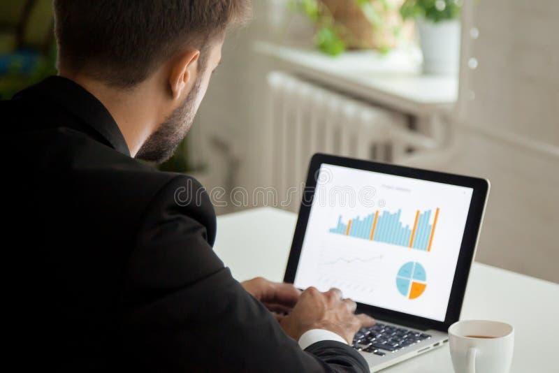Nadenkende zakenman die bij laptop werken die financiële dat analyseren royalty-vrije stock afbeelding