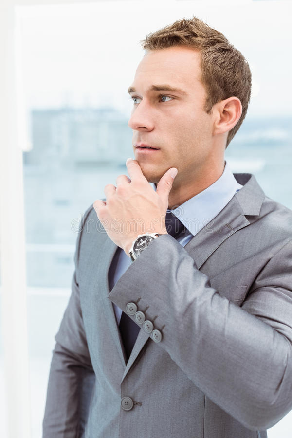 Nadenkende zakenman die weg op kantoor bekijken royalty-vrije stock afbeeldingen