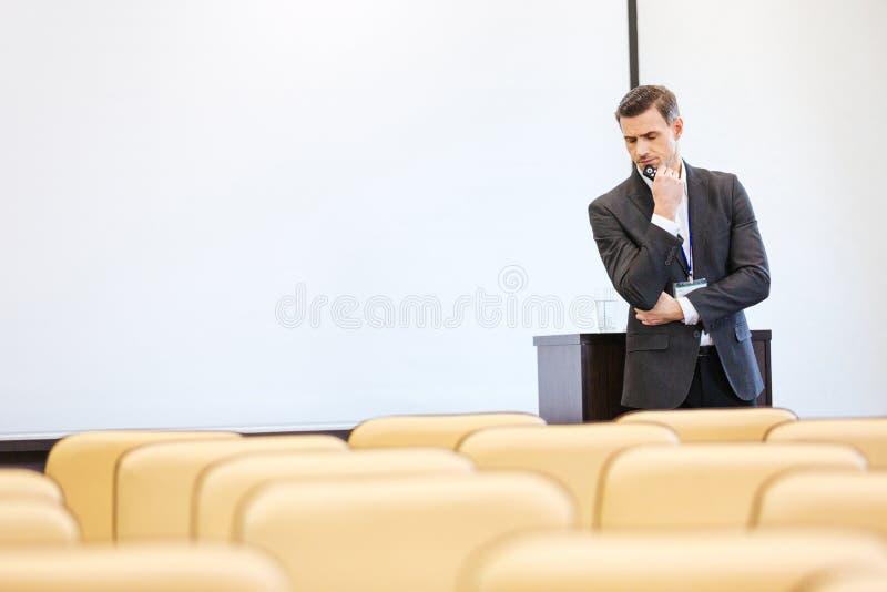 Nadenkende zakenman die zich in lege conferentiezaal bevinden stock afbeelding