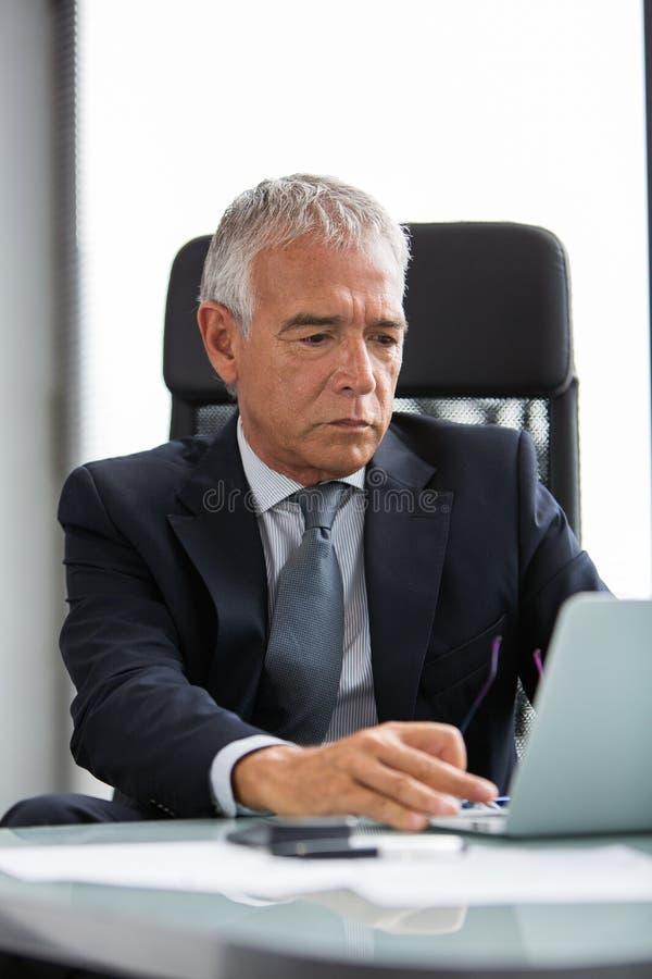 Nadenkende zakenman in het bureau terwijl het gebruiken van laptop computer stock fotografie