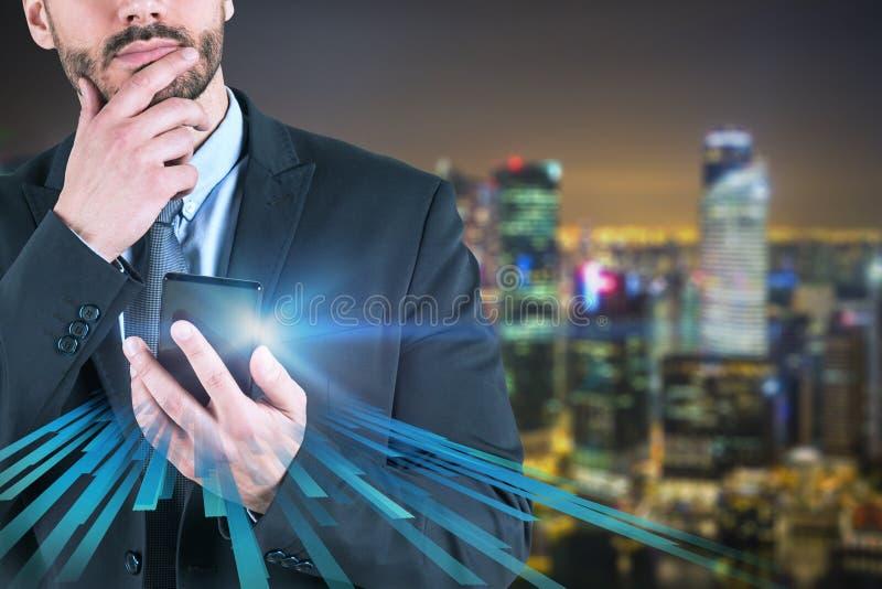 Nadenkende zakenman met telefoon in nachtstad stock fotografie