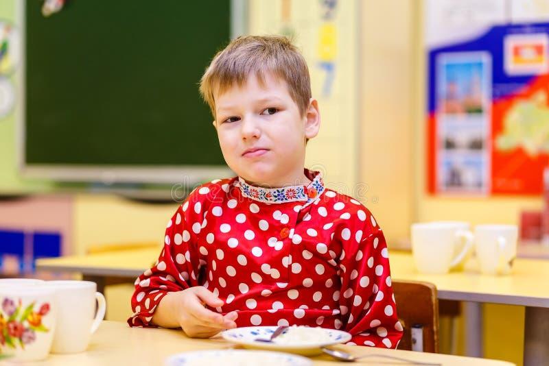 Nadenkende zes-jaar-oude jongenszitting bij een lijst in kleuterschool royalty-vrije stock afbeeldingen