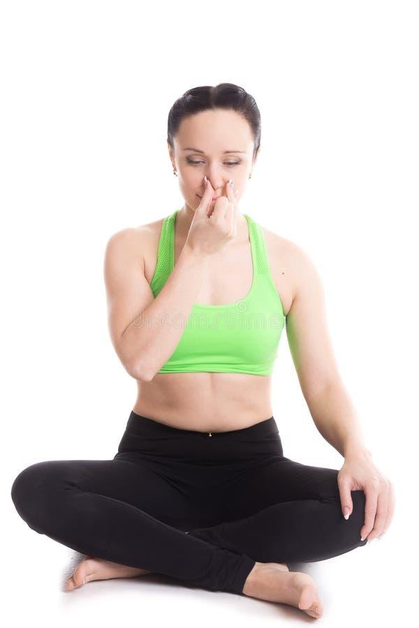 Nadi shodhan pranayama in yoga Easy pose. Calm beautiful girl practicing hatha yoga nadi sodhan pranayama (Alternate Nostril Breathing), sitting cross-legged in stock image
