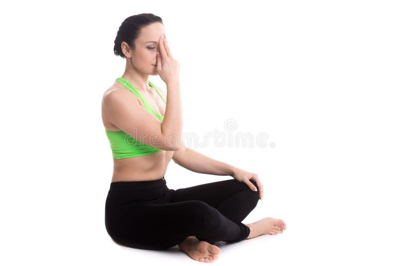 Nadi shodhana pranayama in yoga easy pose. Serene girl practicing yoga nadi shodhana pranayama (Alternate Nostril Breathing), sitting in Easy (Decent, Pleasant royalty free stock photos