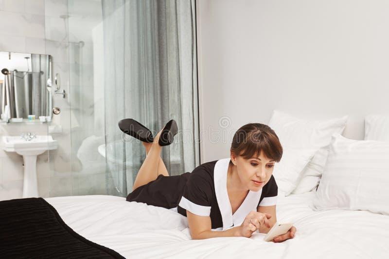 Nadie notará que estoy tomando la rotura Retrato de la criada relajada que miente en uniforme en cama, hojeando en social foto de archivo libre de regalías