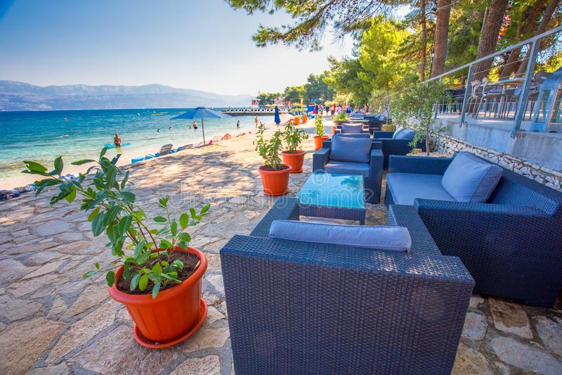 Nadmorski deptak na Brac wyspie z drzewkami palmowymi i turkusu oceanu jasną wodą, Supetar, Brac, Chorwacja zdjęcie stock