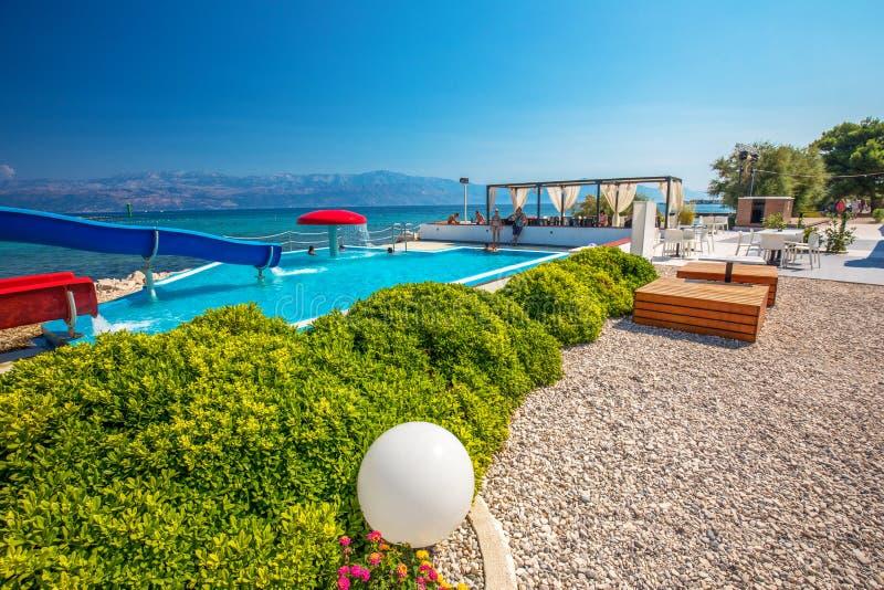 Nadmorski deptak na Brac wyspie z drzewkami palmowymi i turkusu oceanu jasną wodą, Supetar, Brac, Chorwacja zdjęcia royalty free