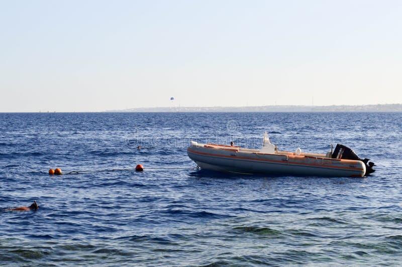 Nadmuchiwana szara łódź, motorowa łódź z silnikiem na solankowym błękitnym morzu przeciw tłu pociesza i odległa góra zdjęcia stock