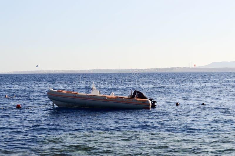 Nadmuchiwana szara łódź, motorowa łódź z silnikiem na solankowym błękitnym morzu przeciw tłu pociesza i odległe góry i błękitny fotografia royalty free