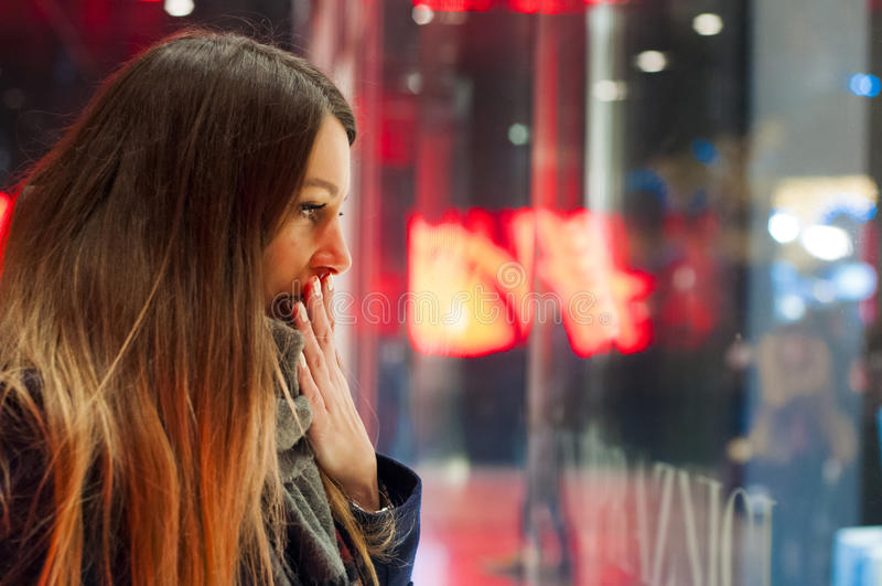 Nadokienny zakupy, kobieta patrzeje sklep Uśmiechnięta kobieta wskazuje przy sklepowym okno przed wchodzić do stora zdjęcie stock