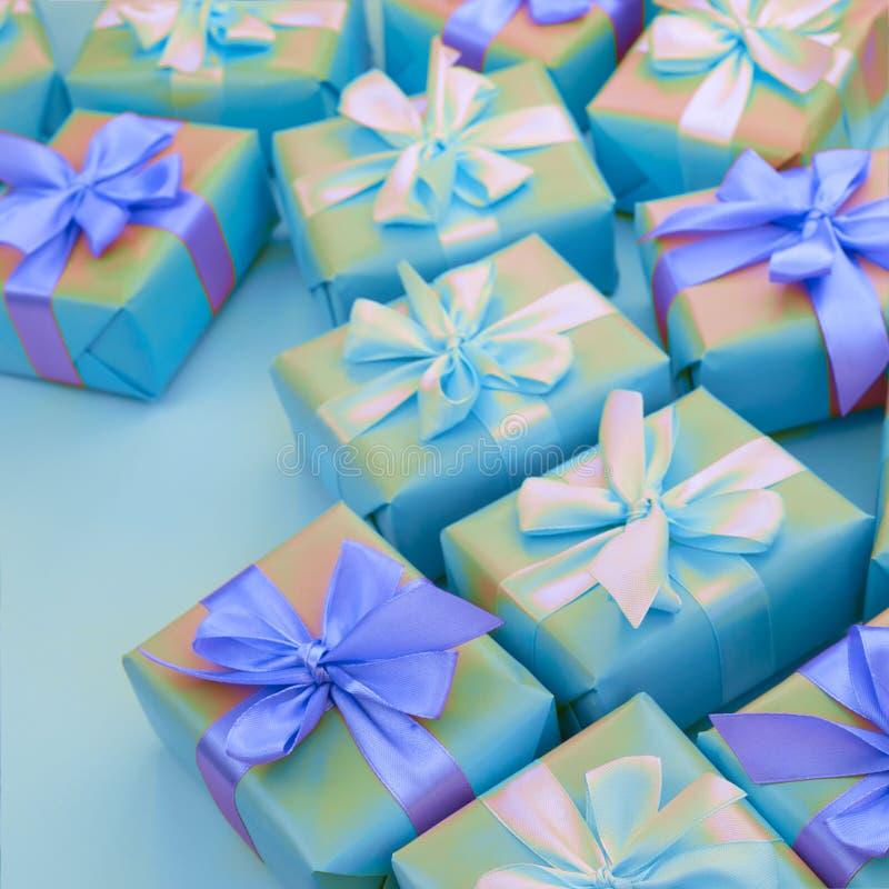 Nadrealizmu wakacyjnego prezenta Dekoracyjni pudełka z menchiami barwią na błękitnym tle fotografia royalty free