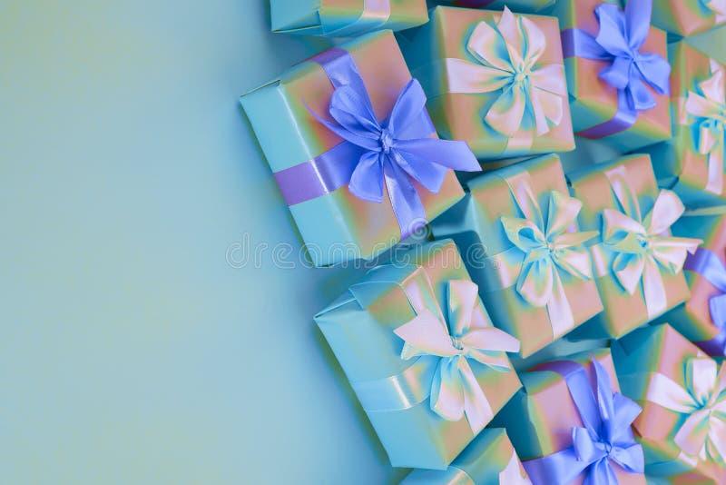 Nadrealizmu wakacyjnego prezenta Dekoracyjni pudełka z menchiami barwią na błękitnym tle zdjęcia stock