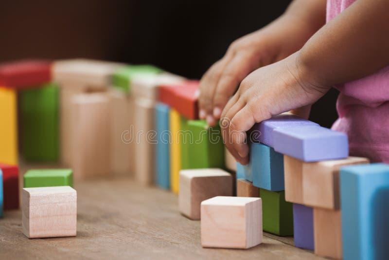 Nadruk bij kind` s hand het spelen met kleurrijke houten blokken stock afbeeldingen