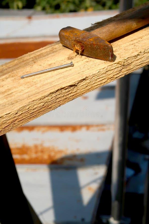 Nadruk houten plank met spijker en hamer op vaag roestmetaal stock foto