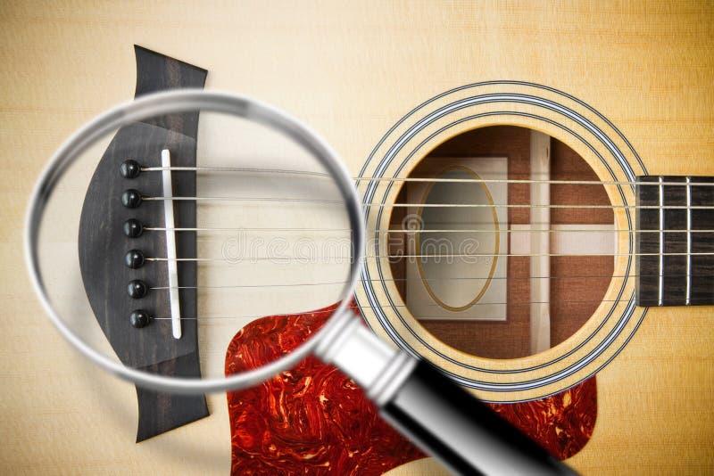 Nadruk op de akoestische gitaar houten die brug - concept met beeld door een vergrootglas wordt gezien stock foto's