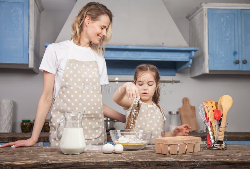 Nadruk op de hand van de dochter die bloem aan de kom toevoegt Mamma en dochter in de keukenkok Mafins stock afbeelding