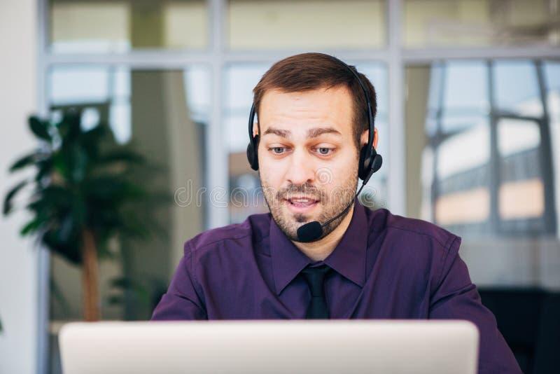 Nadruk op een blije call centreagent met zijn hoofdtelefoon stock foto