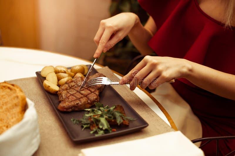 Nadruk op het vlees waar de vork en het mes Het mooie wijfje dient een restaurant bij het het rundvlees striploin lapje vlees van stock fotografie