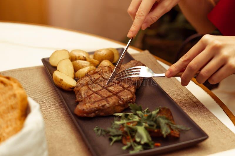 Nadruk op het vlees waar de vork en het mes Het mooie wijfje dient een restaurant bij het het rundvlees striploin lapje vlees van royalty-vrije stock fotografie