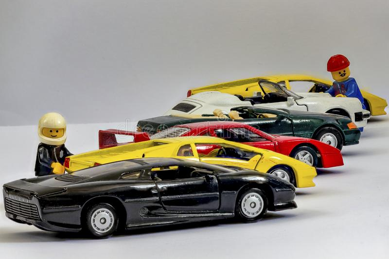 Nadruk-stapelt met Lego-cijfers naast een rij van stuk speelgoed auto's volledig in nadruk royalty-vrije stock afbeeldingen