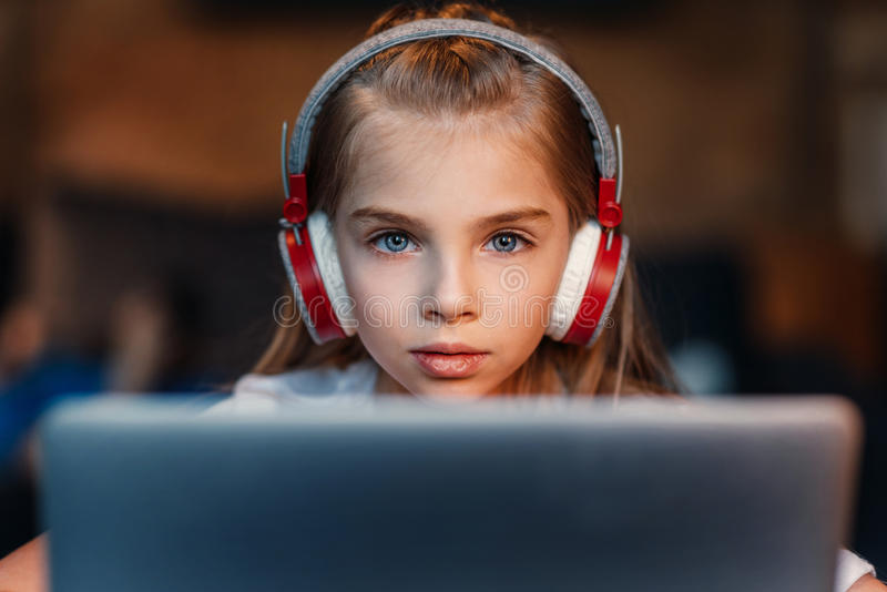 Nadruk van meisje in hoofdtelefoons die laptop met behulp van stock fotografie