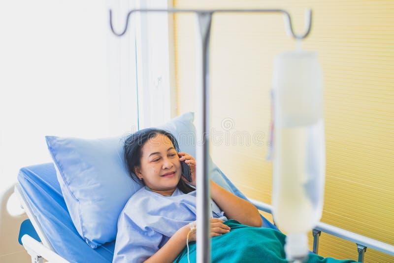 Nadruk van vrouwelijke patiënt op middelbare leeftijd op het bed die de telefoon, in het ruimteziekenhuis met behulp van stock foto's