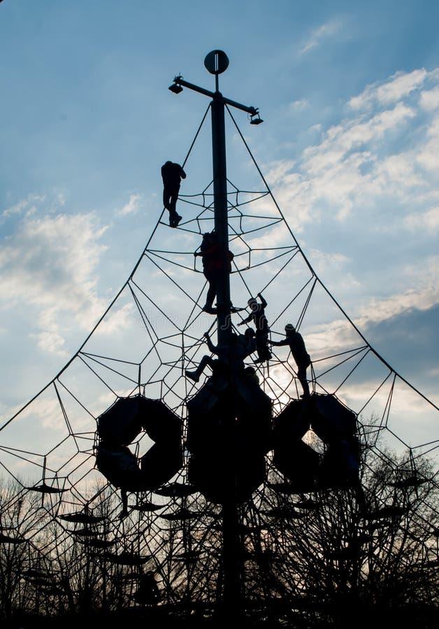 Nadużyta linowa siatka i sylwetki dzieci wspina się na nim fotografia royalty free