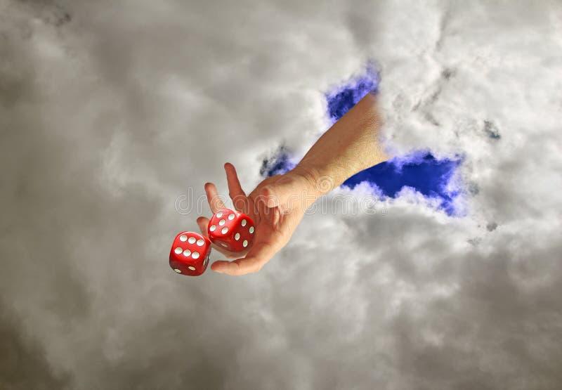 Nadziemska ręka przez chmur stacza się kostki do gry obraz royalty free