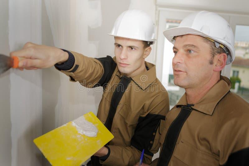 Nadzorca nadzoruje aplikanta używa napełniacz na plasterboard zdjęcie stock
