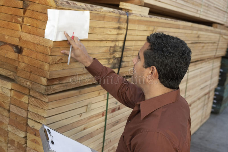 Nadzorca Sprawdza etykietkę Na stercie drewno zdjęcie stock