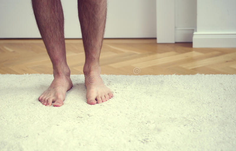 Nadzy cieki mężczyzna pozycja na białym dywanie obrazy royalty free