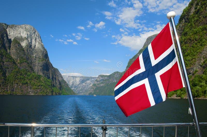 Naeroyfjord et un drapeau national pendant la croisière norvégienne stupéfiante d'Aurlandsfjord et de Naeroyfjord image libre de droits