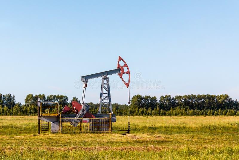 Nafciana pompa pracuje w lecie w zielonym polu obrazy stock