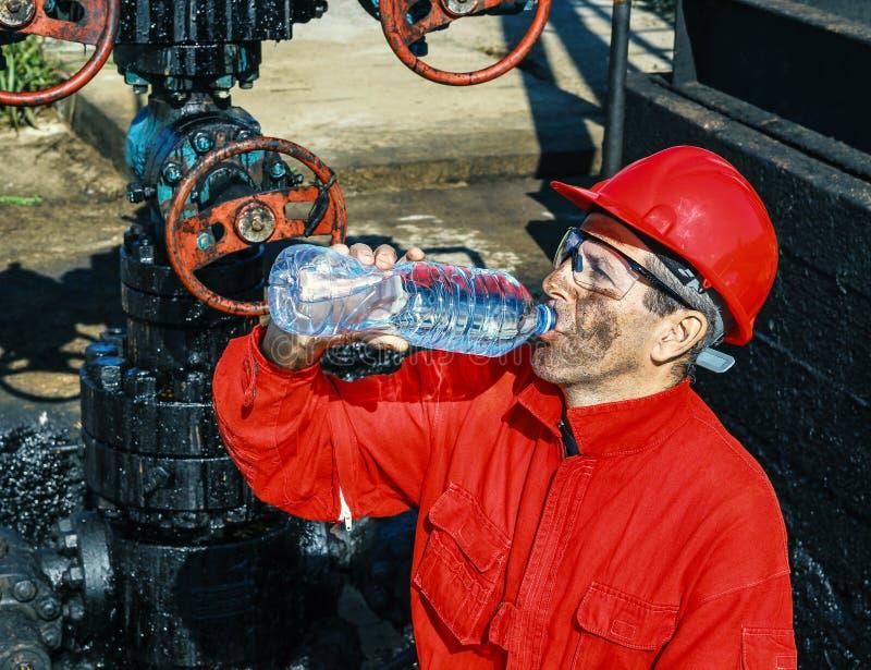 Nafciana pracowników napojów woda Obok szybu naftowego zdjęcie stock