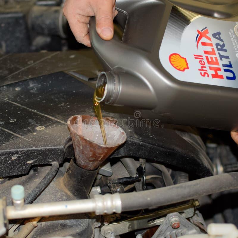 Nafciana zmiana w silniku samochód Wypełniać olej przez leja Samochodowa utrzymanie stacja obraz royalty free
