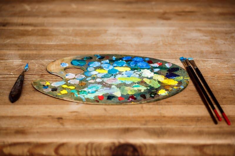 Nafciane farby na palecie i muśnięciach nad drewnianym tłem obrazy royalty free