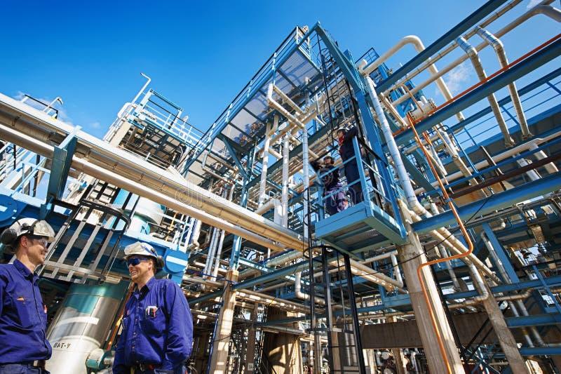 Nafciani pracownicy i przemysłowa rafineria fotografia royalty free