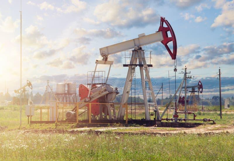 Nafciany pumpjack na niebie chmurnieje tło Szybu naftowego przemysł fotografia stock