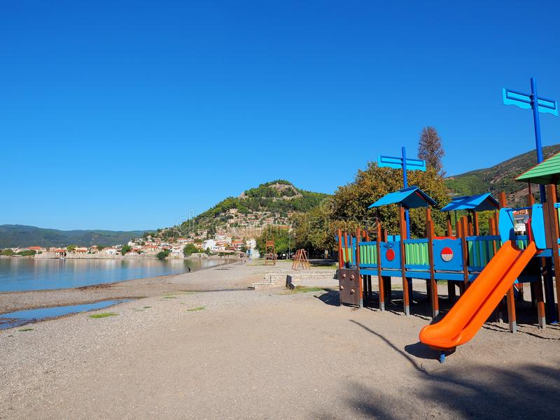 Nafpaktos Beach and Castle, Greece. View of the city beach in Nafpaktos, Greece, with colourful childrens play equipment and the ancient Venetian castle on the stock images